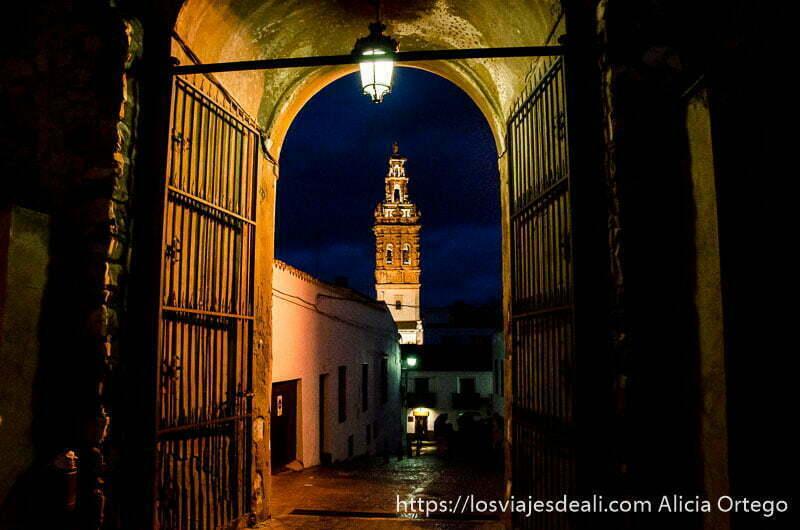 calle con arco y torre al fondo por la noche iluminada en jerez de los caballeros