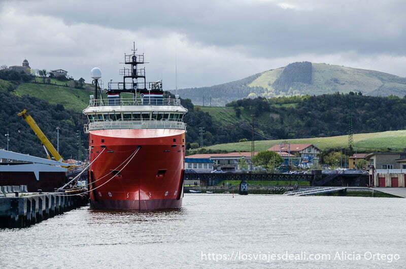 barco de casco rojo en la ría de zumaia con montes verdes detrás