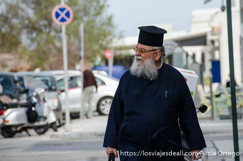 cura ortodoxo con hábito negro y barba blanca andando por la capital de naxos con bolsas de la compra