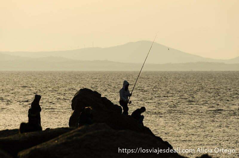 pescadores en rocas con luz dorada de fondo en la capital de naxos