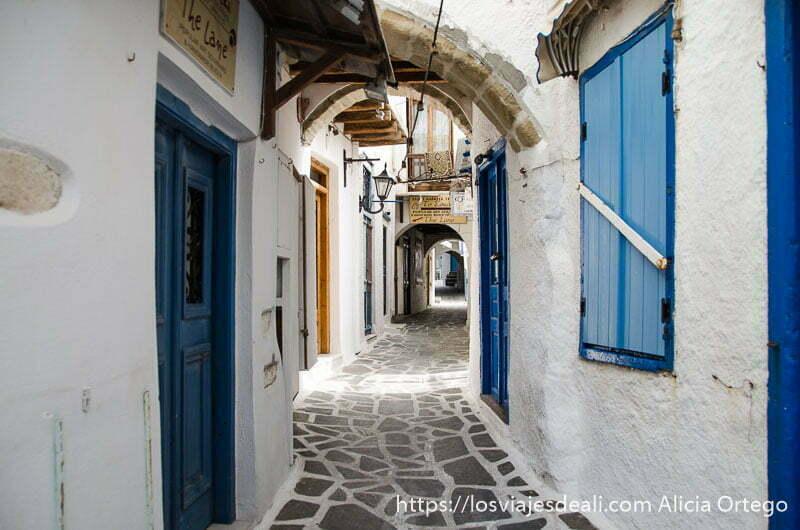 calle de paredes blancas y puertas y ventanas azules en la capital de naxos