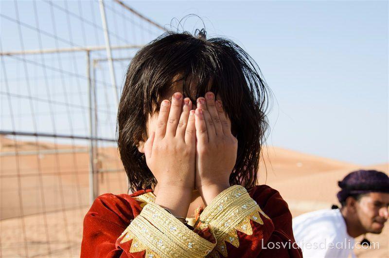 niña tapándose la cara con las dos manos en el desierto de wahiba