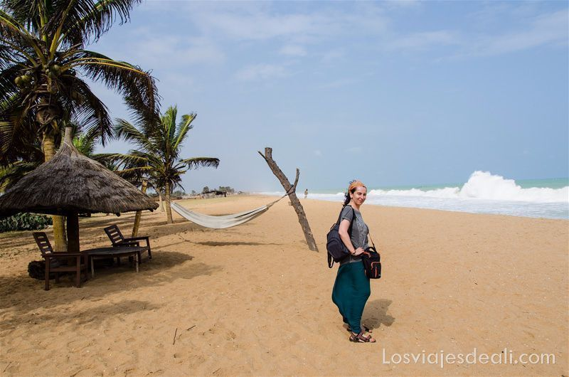 yo posando en una playa de benin con palmeras a mi espalda y mar con olas enfrente