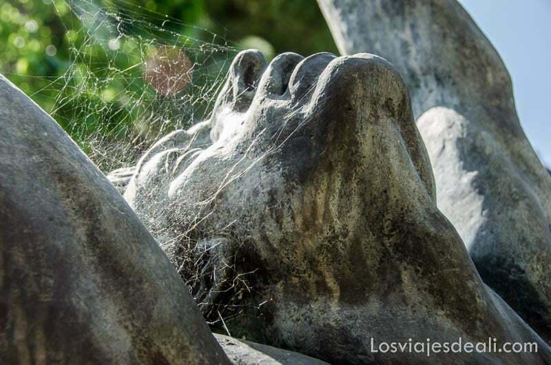 cabeza de estatua mirando hacia el cielo con telarañas en la cara en el jardín de can prunera de Sóller