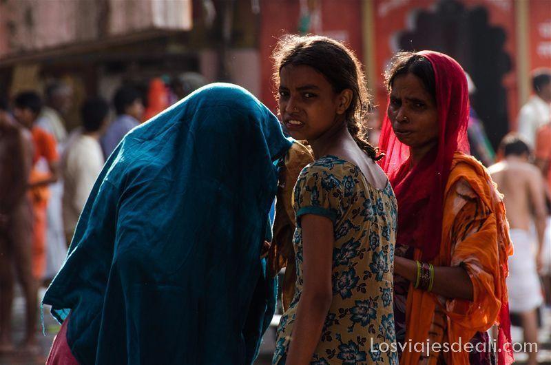 niña india con coleta y dos mujeres al lado con velos uno de color azul y otro rojo foto del 8 de marzo