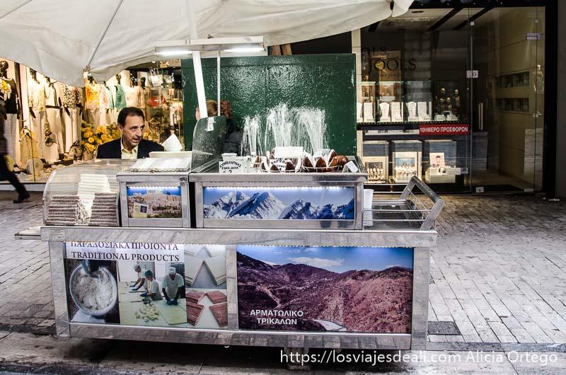 vendedor de coco sentado en su puesto en el centro de atenas