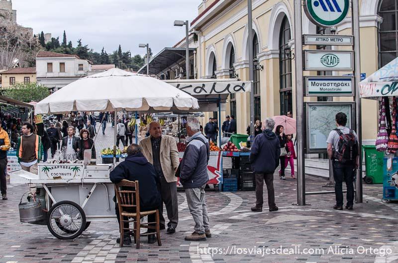 señores mayores hablando bajo sombrilla de puesto de comida en plaza monastiraki lugares de interés en atenas