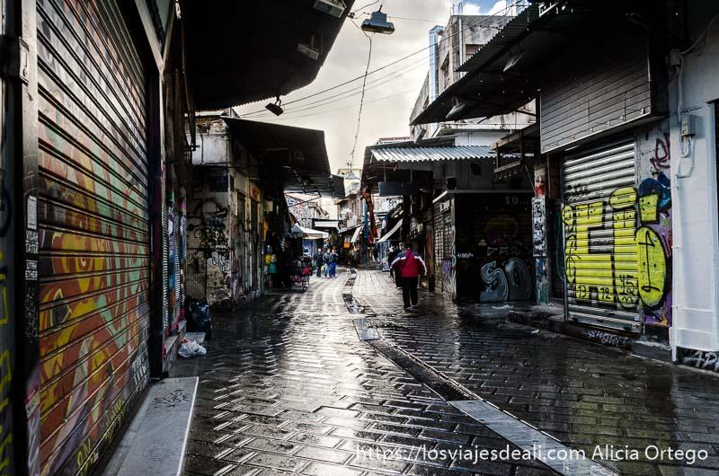 calle con tiendas cerradas y suelo mojado por la lluvia lugares de interés en atenas