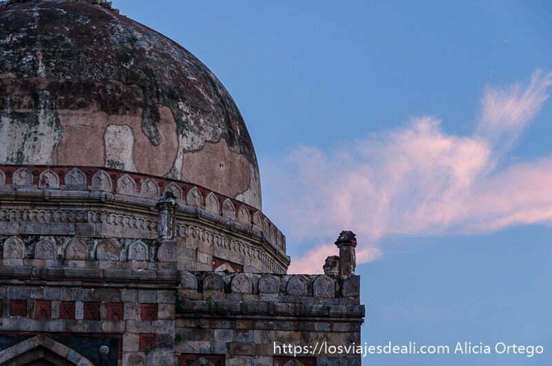 cúpula de antiguo templo de piedra con nubes rosadas por atardecer qué ver en delhi