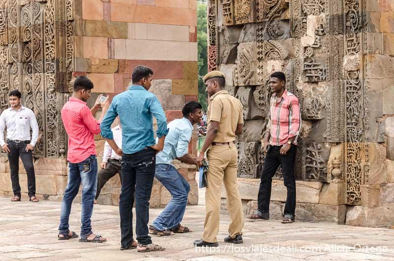 grupo de chicos haciéndose fotos en el qtub minar uno con uniforme de policía qué ver en delhi