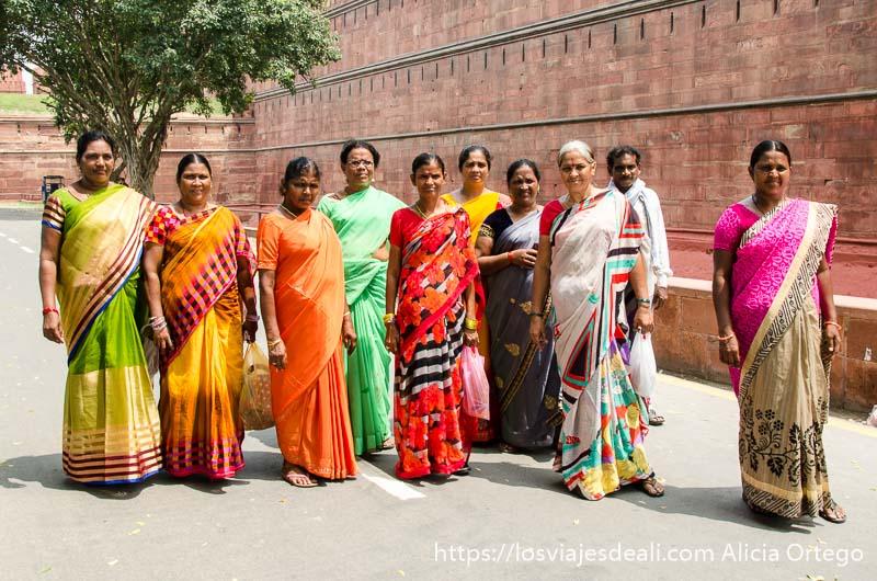 grupo de 9 mujeres con saris de colores visitando el fuerte rojo qué ver en delhi