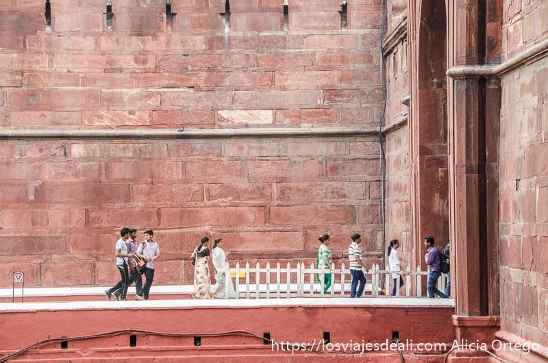 gente andando por la pasarela que lleva a la puerta principal del fuerte rojo qué ver en delhi