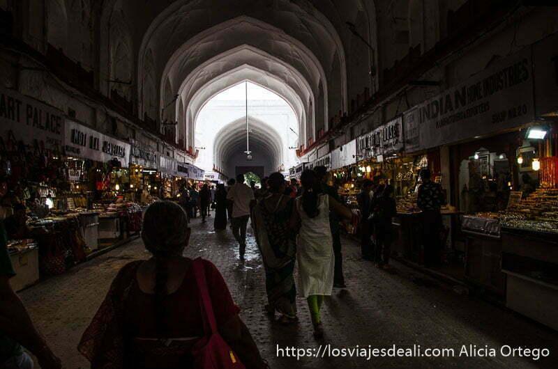 pasaje oscuro lleno de tiendas con techo en arcos y al final luz qué ver en delhi