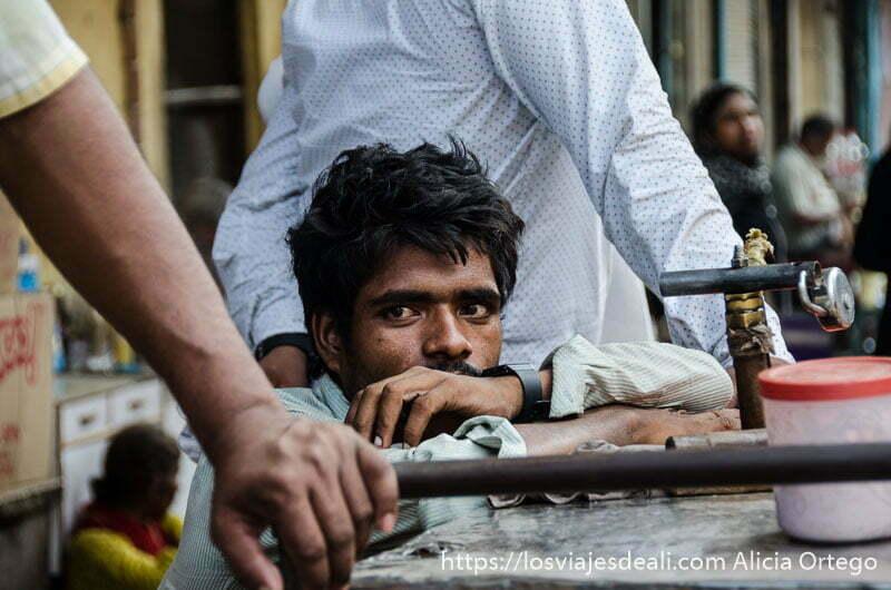chico de mirada profunda apoyado en mostrador qué ver en delhi. Retratos de India.