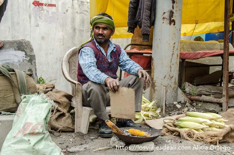 hombre asando mazorcas de maíz en parada en carreteras del himalaya indio