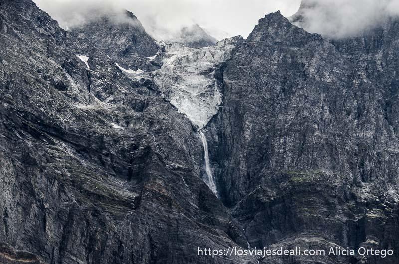 paredes de roca gigantescas con un glaciar y cascada en su vértice carreteras del himalaya indio