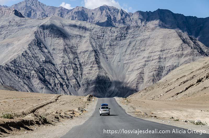 coche avanzando por carretera recta con gran montaña al fondo carreteras del himalaya indio