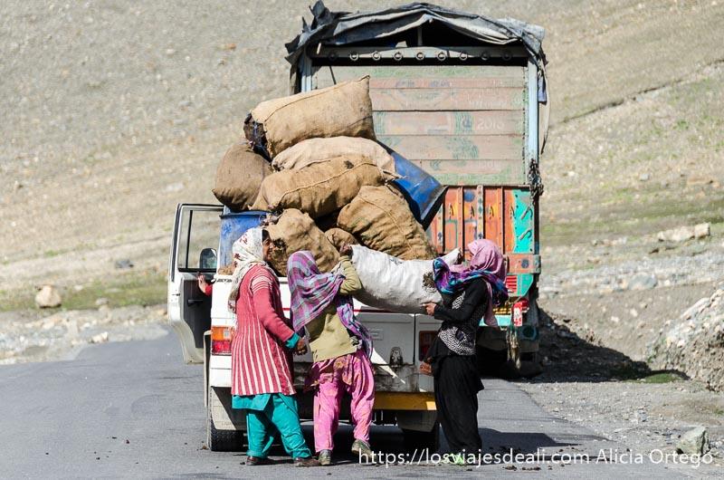 tres mujeres cargando pesados sacos en un camión carreteras del himalaya indio