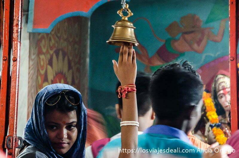 mano alzándose para tocar campana antes de entrar a ver al dios hanuman en haridwar