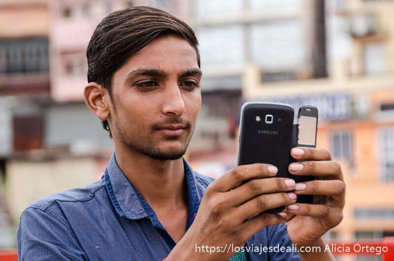 chico con pelo peinado a un lado haciéndose un selfie con su móvil en hardiwar