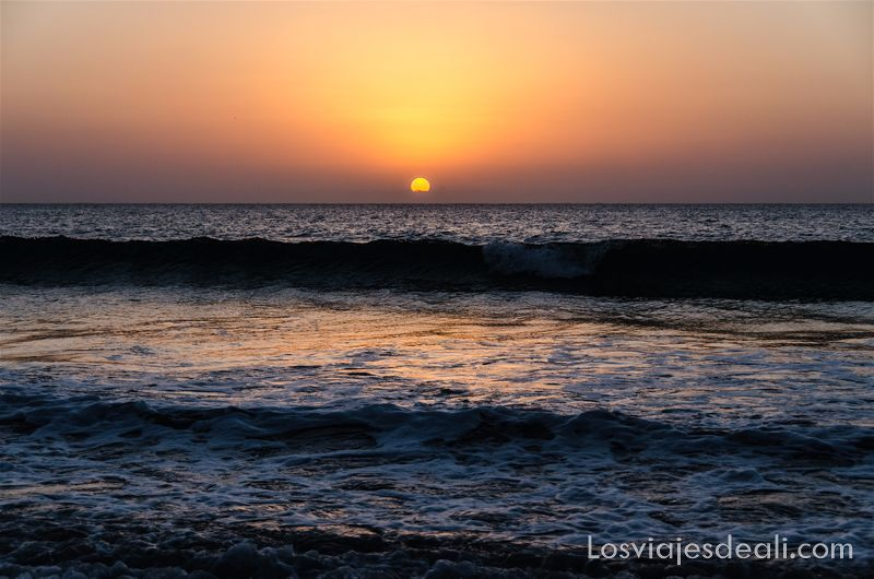 amaneceres del mundo: el sol saliendo por el horizonte del mar iluminando las olas