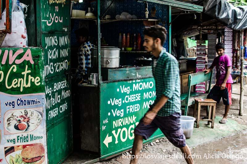 puesto de momos y sandwiches pintado de verde con un chico pasando por delante en rishiskeh