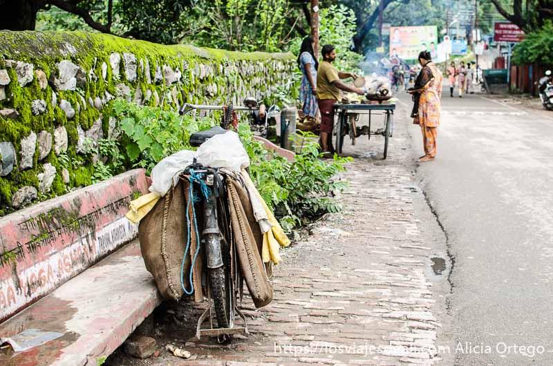 bicicleta apoyada en un banco y al fondo pequeño puesto de comida con clientes en rishiskesh