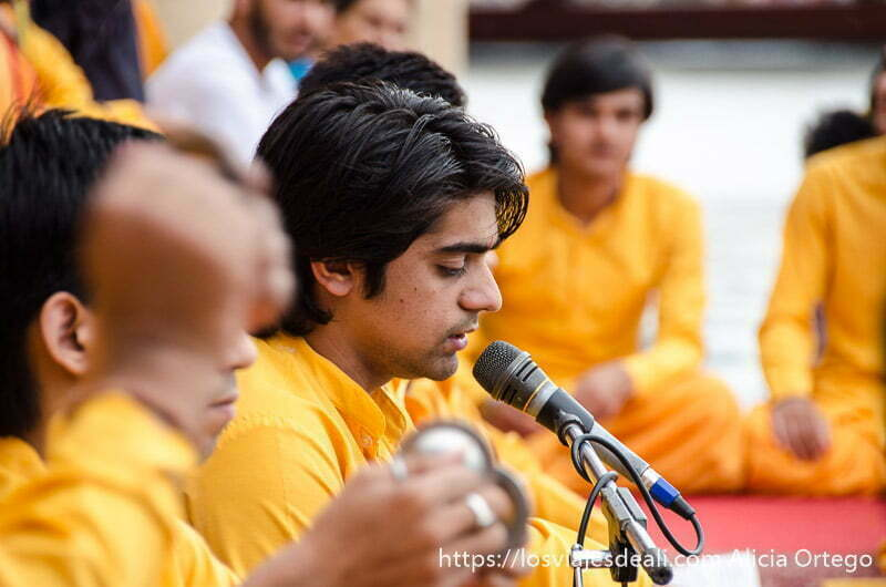joven vestido de naranja cantando ante un micrófono en rishikesh