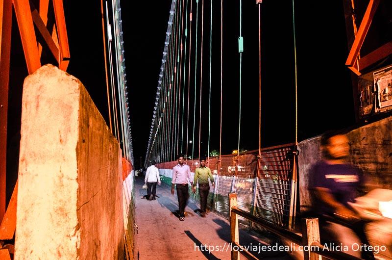 puente de rishikesh por la noche con una moto pasando