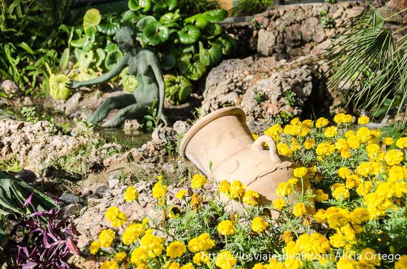 ánfora y estatua de bronce de mujer desnuda entre flores del jardín botánico de torremolinos