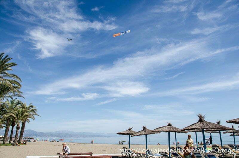 playa con sombrillas de paja, palmeras, y algunas nubes un fin de semana diferente en torremolinos