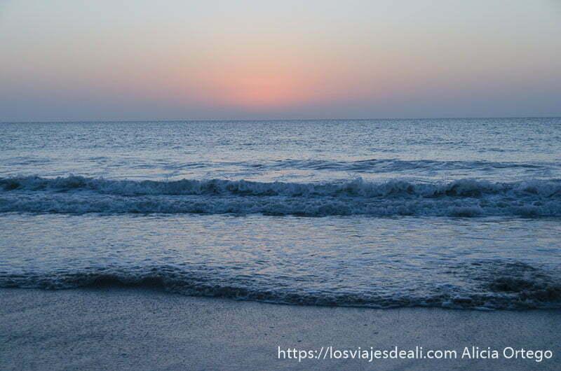 sol oculto por neblina sobre mar con pequeñas olas desiertos de oman