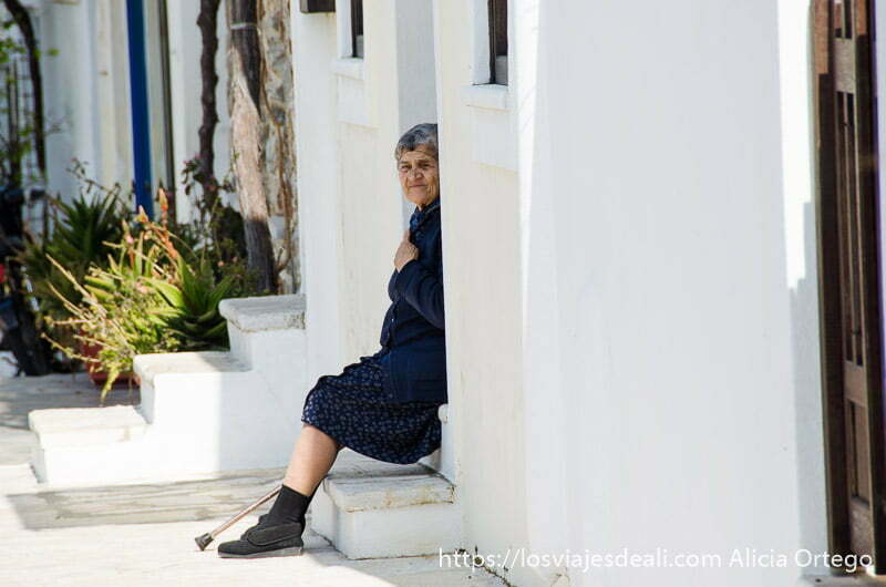anciana con redecilla en la cabeza sentada en la puerta de su casa encalada
