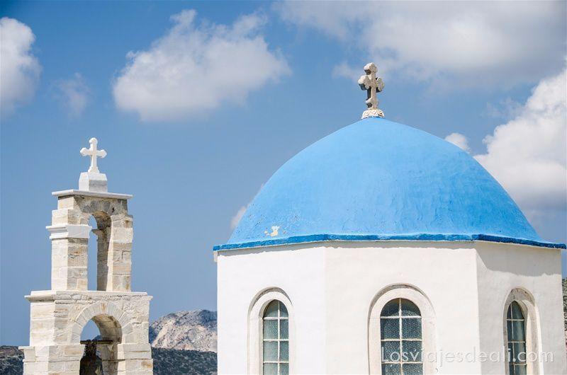 cúpula de iglesia pintada de azul y campanario de piedra con cruz blanca en Filoti