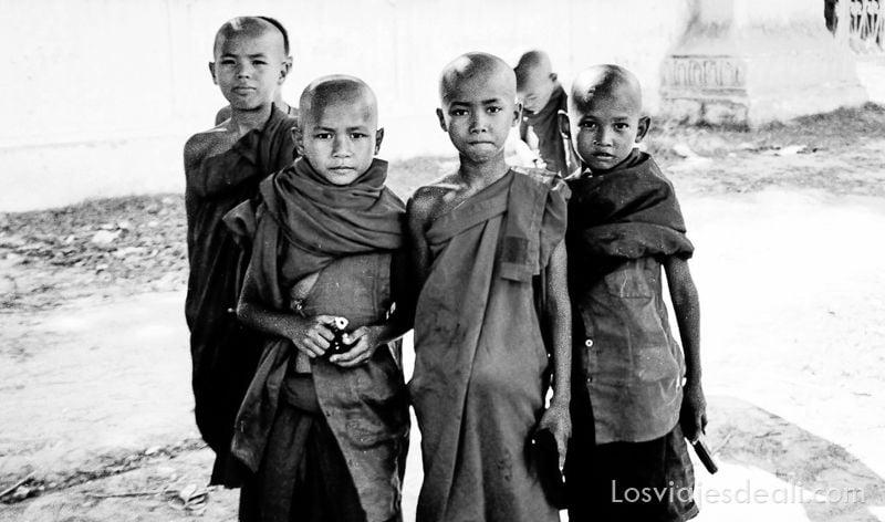 cuatro niños monje budistas con cabeza afeitada y pistolas de juguete en la mano mirando a la cámara.
