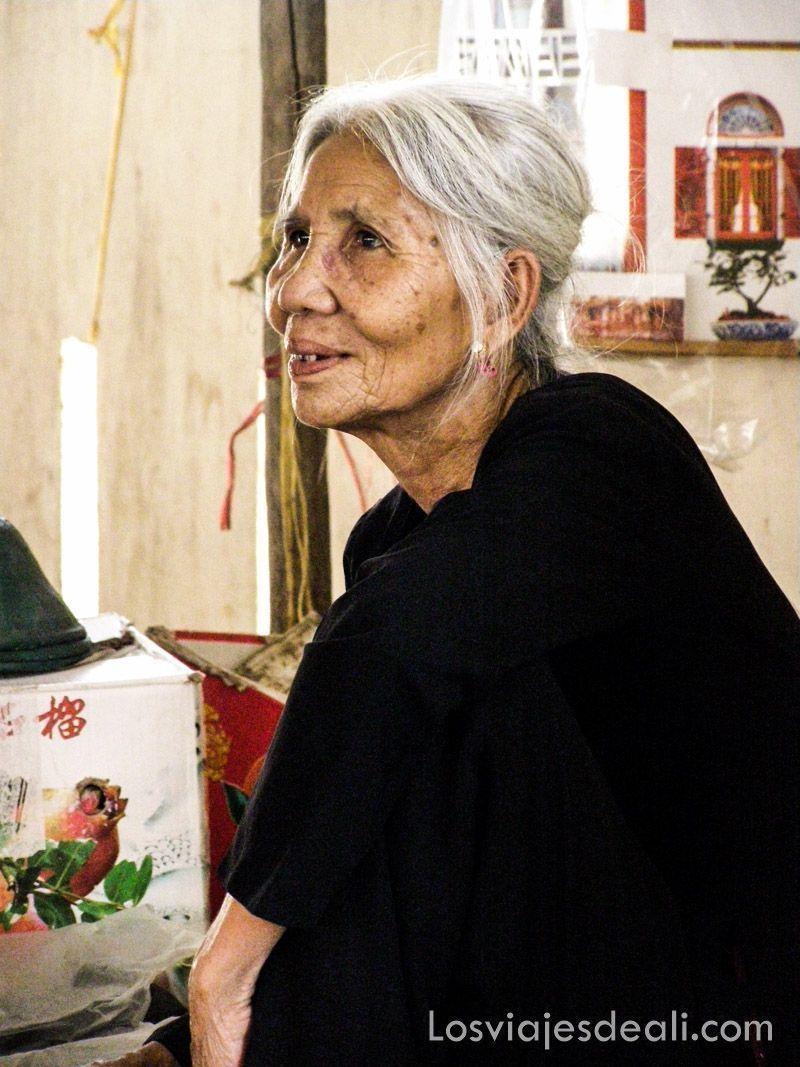 Mujer vietnamita mayor vestida de negro con pelo largo blanco recogido en un moño bajo, de perfil y sonriente
