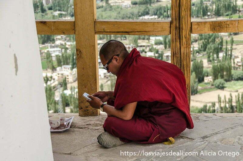 monje tibetano sentado en el suelo concentrado en su smartphone y con gafas de sol
