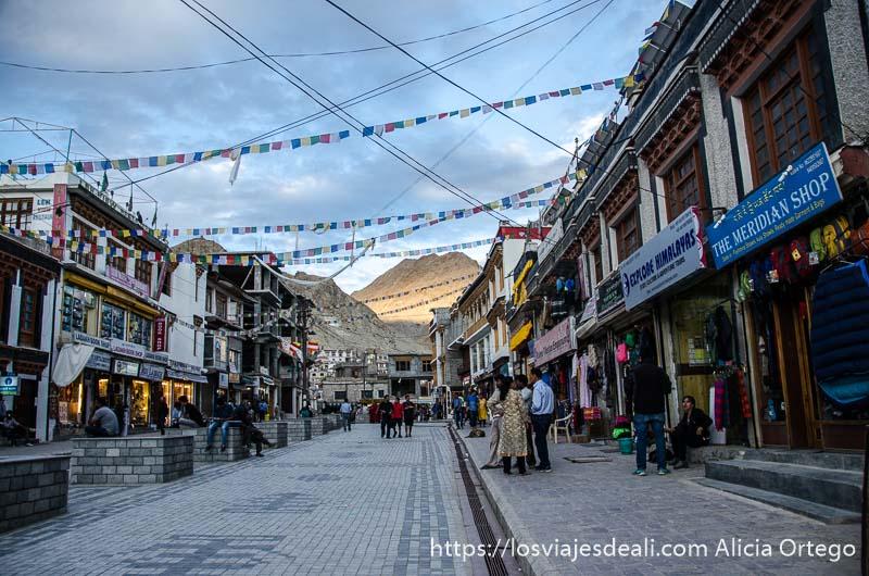 calle main bazaar de Leh con montaña iluminada por sol de atardecer al fondo