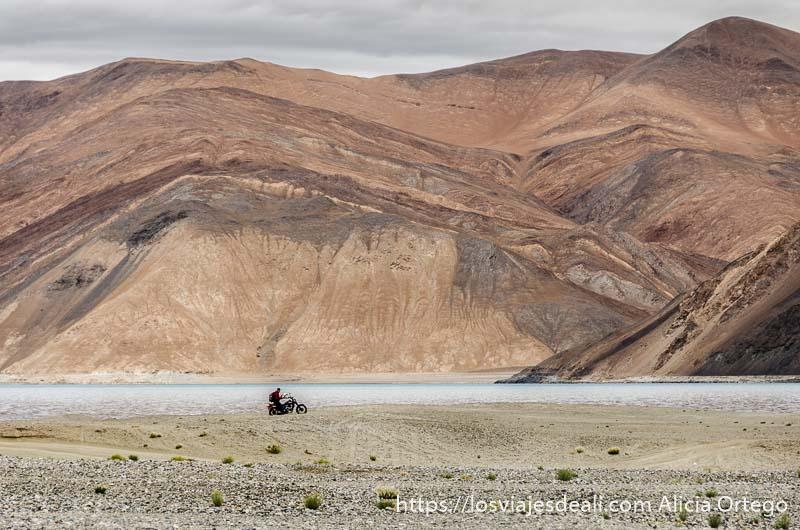 moto rodando junto al lago pangong con grandes montañas de colores ocres detrás