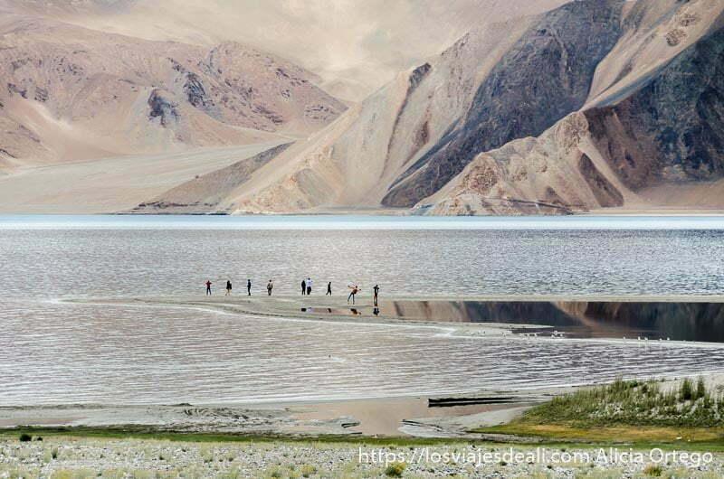 turistas haciendo posturas junto al lago pangong reflejándose en el agua