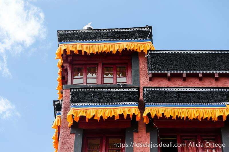 fachada de monasterio tibetano pintada de colores con cortinillas en las ventanas valle del indo