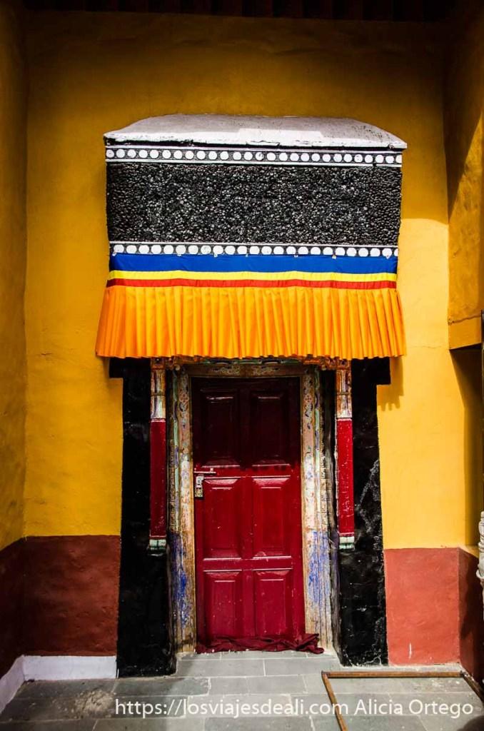 puerta de monasterio budista con pared pintada de amarillo y rojo brillantes valle del indo