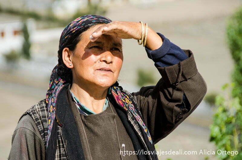 mujer tibetana con pañuelo en la cabeza mira a lo lejos protegiéndose del sol con la mano valle del indo