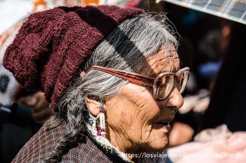 anciana tibetana con gafas y gorro de lana en una conferencia del dalai lama