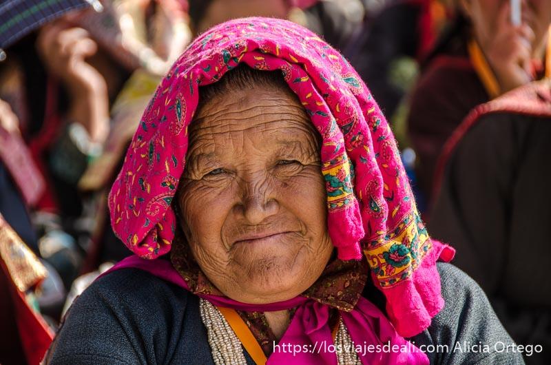 mujer posando con tela de color rosa sobre la cabeza una conferencia del dalai lama