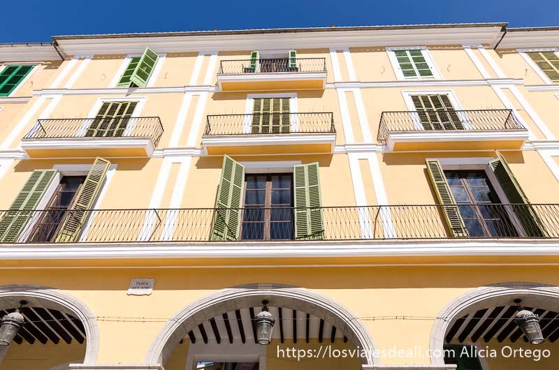 fachada pintada de amarillo con balcones verdes en palma de mallorca