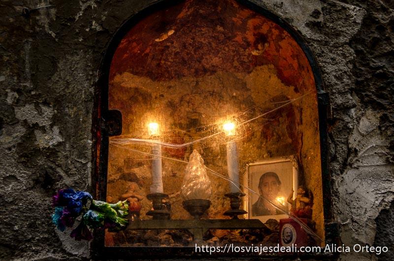 virgen en hornacina con velas encendidas en una calle de nápoles