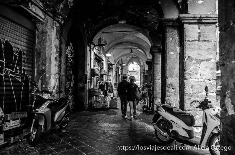 pareja paseando por soportales de piedra paseos por nápoles