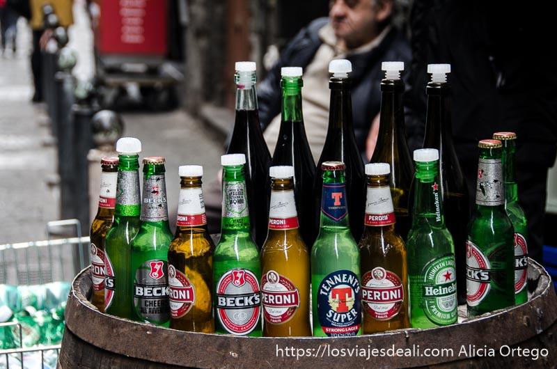 barril con parte superior llena de botellas de cerveza de distintas marcas en una calle de nápoles