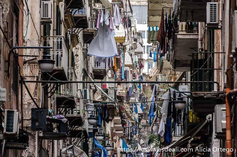 calle llena de balcones con ropa tendida y antenas parabólicas en nápoles